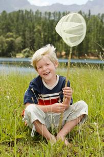 Boy (7-9) sitting in field holding butterfly net front view.の写真素材 [FYI03648030]