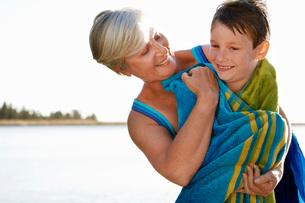 Grandmother hugging Grandson (7-9) by lake.の写真素材 [FYI03648047]
