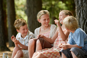 Four children (7-9) sitting in forest laughing.の写真素材 [FYI03648048]