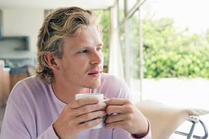 Man having coffee in living roomの写真素材 [FYI03648079]