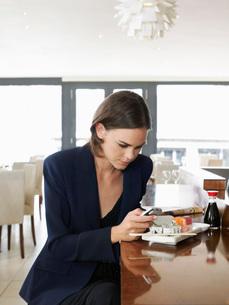 Woman text messaging in sushi restaurantの写真素材 [FYI03648123]