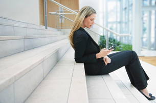Businesswoman text messaging on steps outside officeの写真素材 [FYI03648134]