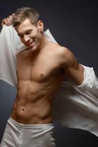 Man wearing underwear putting on shirt portraitの写真素材 [FYI03648149]
