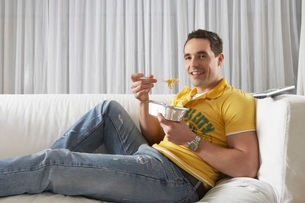 Young man sitting on sofa eating noodles from takeaway trayの写真素材 [FYI03648190]