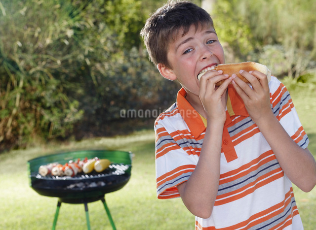 Portrait of boy (10-12) eating frankfurter barbecue grill inの写真素材 [FYI03648209]