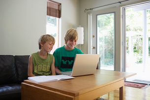 Brothers (6-11) sitting at table using laptop smilingの写真素材 [FYI03648226]