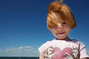 Portrait of ginger haired girl (5-6) against blue skyの写真素材 [FYI03648233]