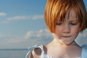 Young girl (5-6) at ocean close-up portraitの写真素材 [FYI03648245]