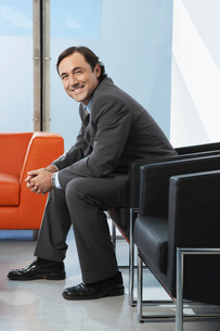 Business man sitting in leather chair in office portraitの写真素材 [FYI03648255]