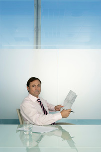 Business man holding document at table in conference room poの写真素材 [FYI03648257]