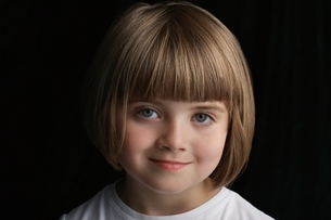 Girl (5-6) on black background portrait close-upの写真素材 [FYI03648299]
