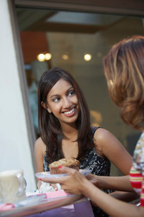Two women chatting at cafe tableの写真素材 [FYI03648326]