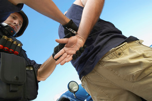 Police man putting handcuffs on criminalの写真素材 [FYI03648382]