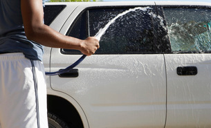 Man spraying car with hose mid sectionの写真素材 [FYI03648384]