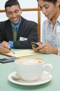Business man and woman at cafe focus on cappuccino in foregrの写真素材 [FYI03648396]