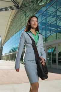 Businesswoman walking past office buildingの写真素材 [FYI03648401]