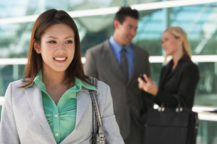 Businesswoman smiling with colleagues in background outdoorsの写真素材 [FYI03648418]