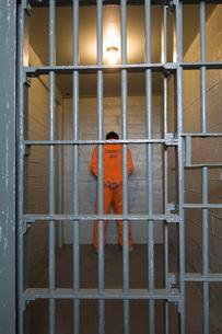Prisoner standing in prison cellの写真素材 [FYI03648469]
