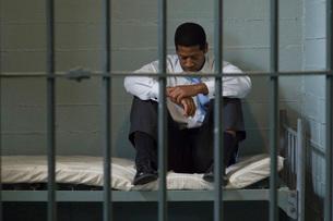 Prisoner sitting in his prison cellの写真素材 [FYI03648474]