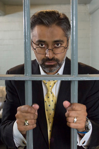 Businessman standing behind prison cell barsの写真素材 [FYI03648478]