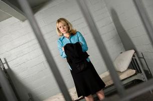 Female criminal behind bars in jailの写真素材 [FYI03648552]