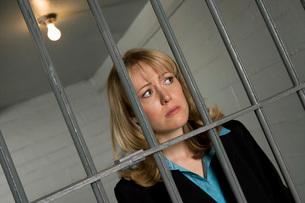 Female criminal behind bars in jailの写真素材 [FYI03648553]