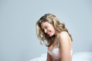 Young woman in underwear smiling on bedの写真素材 [FYI03648587]
