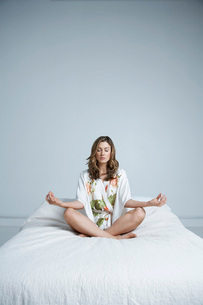 Young woman in dressing gown meditating in bedの写真素材 [FYI03648592]