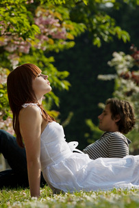 Young Couple Sitting in the Grassの写真素材 [FYI03648747]