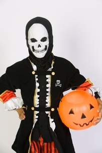 Portrait of boy (7-9) wearing skeleton mask with jack-o-lantの写真素材 [FYI03648828]