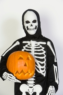 Portrait of child (7-9) wearing skeleton costume with jack-oの写真素材 [FYI03648833]
