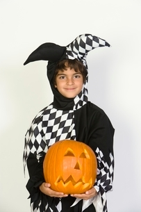 Portrait of boy (7-9) wearing jester costume with jack-o-lanの写真素材 [FYI03648836]