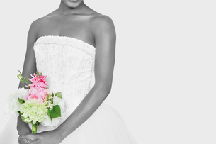 Midsection of bride holding bouquet over gray backgroundの写真素材 [FYI03648952]