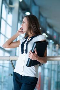 Businesswoman on mobile phone holding folderの写真素材 [FYI03649013]