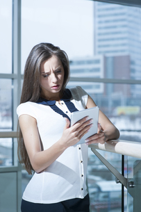Concerned businesswoman looking at tablet deviceの写真素材 [FYI03649014]