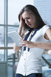 Shocked businesswoman reading tablet deviceの写真素材 [FYI03649015]