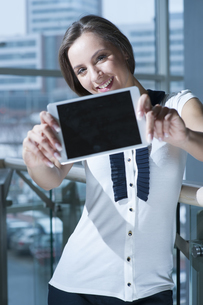 Businesswoman holds up tablet device to cameraの写真素材 [FYI03649018]