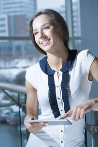 Businesswoman holding tablet device and smilingの写真素材 [FYI03649020]