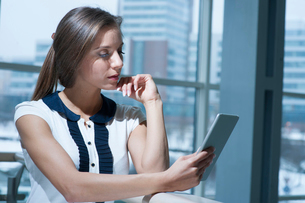 Pensive businesswoman reading from digital tabletの写真素材 [FYI03649022]