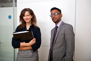 Work colleagues stand together in meeting room smilingの写真素材 [FYI03649046]