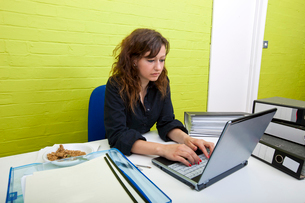 Caucasian young woman working on her laptop computer at her deskの写真素材 [FYI03649059]