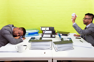 Indian businessman throwing paper at his sleeping twinの写真素材 [FYI03649083]