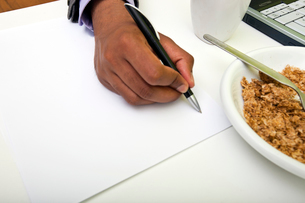 Close up of Indian mans hands writing on paper next to cerealの写真素材 [FYI03649087]