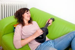 Young woman lying on couch playing ukuleleの写真素材 [FYI03649097]