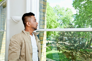 Young Indian man looking out windowの写真素材 [FYI03649102]