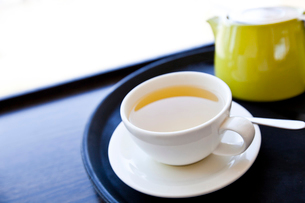 Cup of Green Tea on a tray with saucer and spoonの写真素材 [FYI03649241]