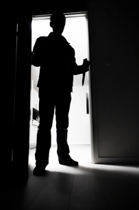 Full-length of thief with knife entering into dark roomの写真素材 [FYI03649263]
