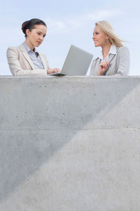 Low angle view of businesswoman using laptop while standing with coworker on terrace against skyの写真素材 [FYI03649274]