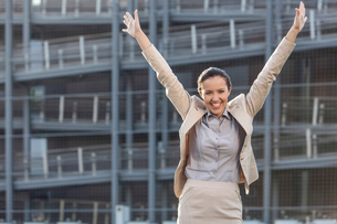 Excited young businesswoman with arms raised standing against office buildingの写真素材 [FYI03649278]