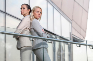 Serious young businesswomen standing back to back at office railingの写真素材 [FYI03649293]